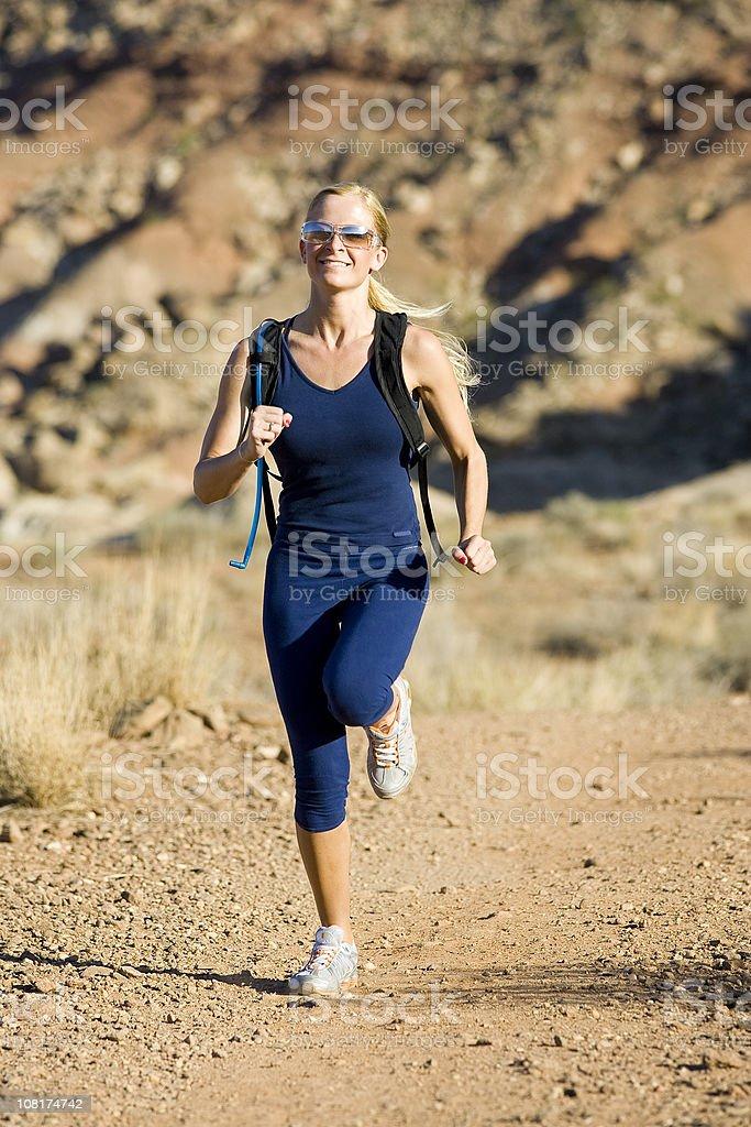 Young Woman Athlete Running Through Desert
