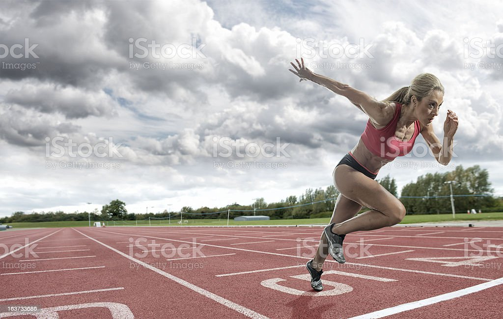 Young woman athlete taking off on a running track royalty-free stock photo
