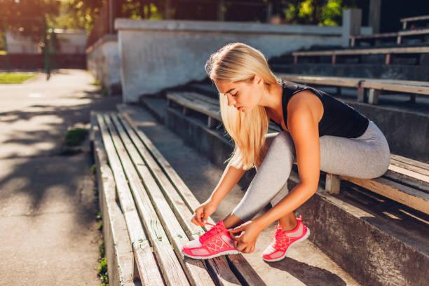 junge sportlerin turnschuhe sitzen auf bank am sportplatz im sommer zu binden. vorbereitung für die ausbildung - sitzbank schuhe stock-fotos und bilder