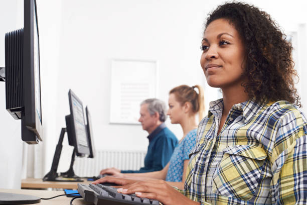 young woman attending computer class - adult education stock pictures, royalty-free photos & images