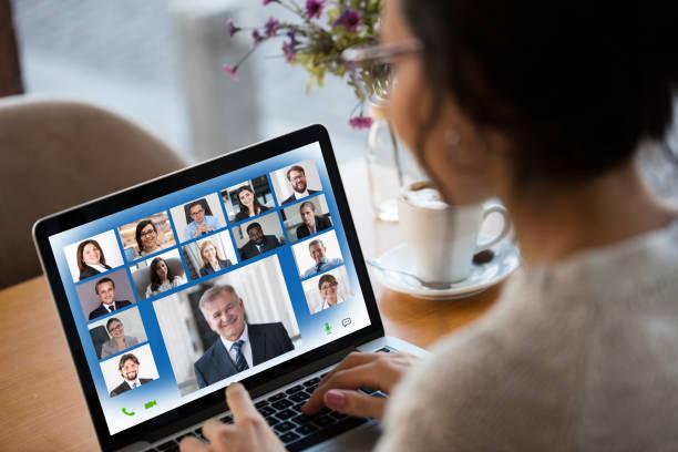 young woman attending video conference on laptop computer - coinvolgimento dei dipendenti foto e immagini stock