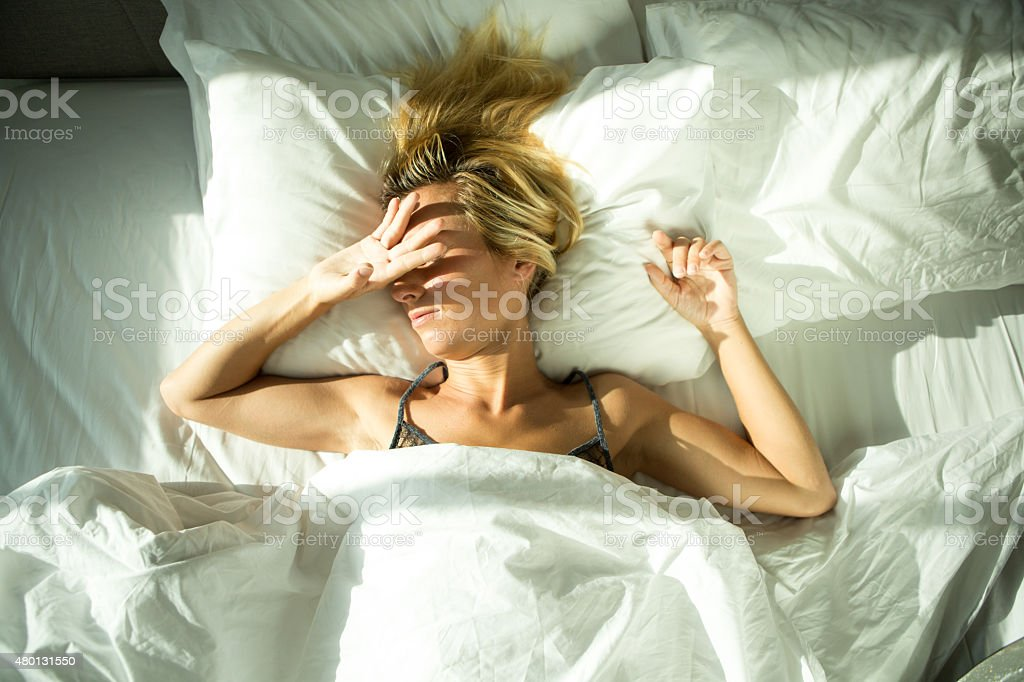 Young woman awaked by sunlight coming in hotel room stock photo