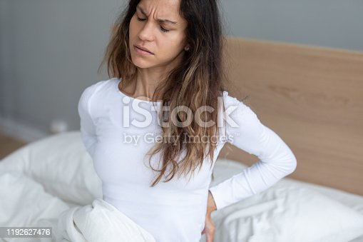 821012164istockphoto Young woman awakening feeling lower back pain 1192627476