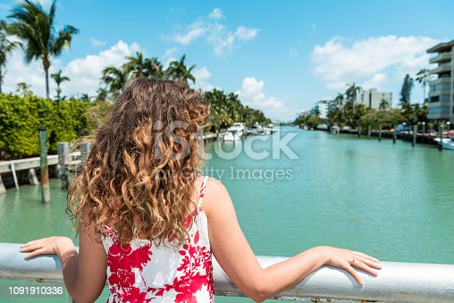 Young woman back with curly or wavy beach hair in red dress standing leaning on bridge railing in Bal Harbour, Miami Florida with green ocean Biscayne Bay