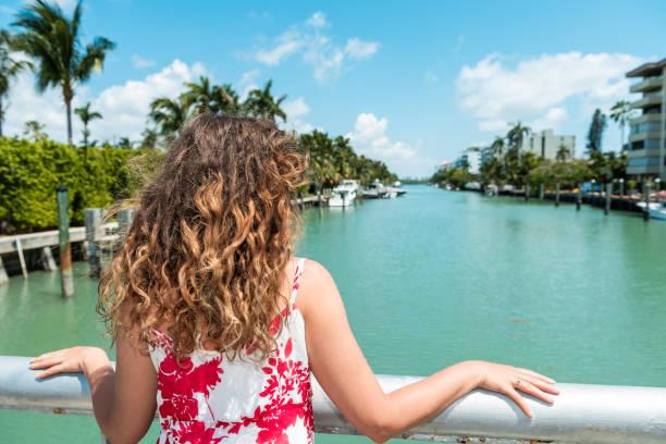junge frau mit strand lockiges oder welliges haar im roten kleid stehen, stützte sich auf geländer in bal harbour, miami, florida mit grünen ozean biscayne bay brücke zurück - haare ohne lockenstab wellen stock-fotos und bilder