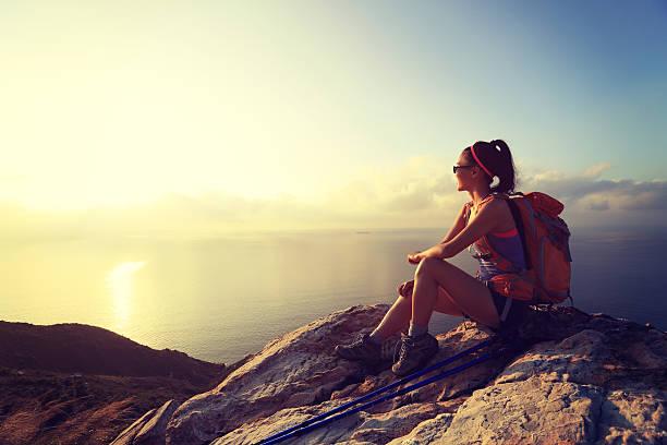 rucksacktourist junge frau bei sonnenaufgang am berggipfel - damen top gold stock-fotos und bilder