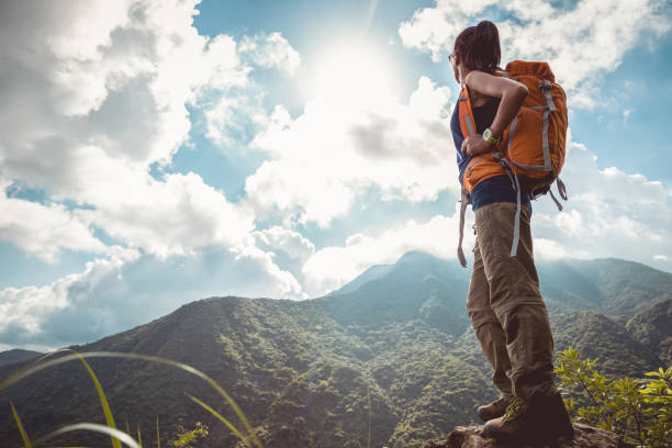 Young woman backpacker enjoy the beautiful view at mountain peak stock photo