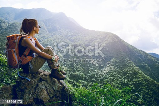 Young woman backpacker enjoy the view at mountain peak