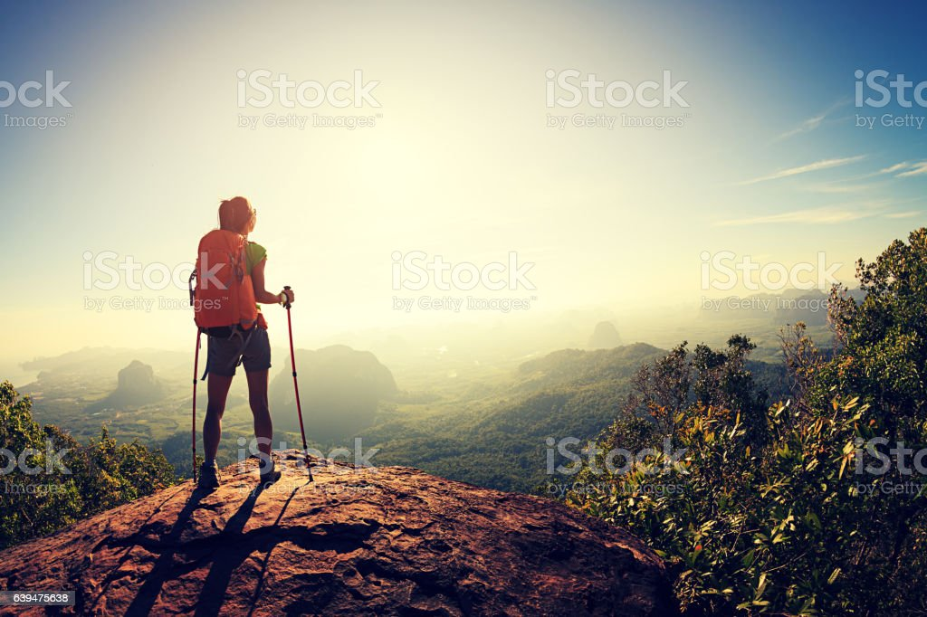 young woman backpacker hiking at seaside mountain cliff stock photo