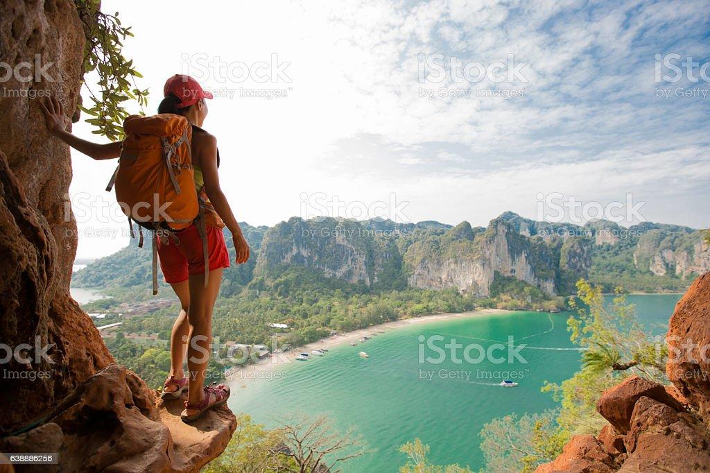 young woman backpacker hiking on seaside mountain stock photo