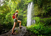 young woman backpacker looking at the waterfall in jungles. Ecotourism concept image travel girl