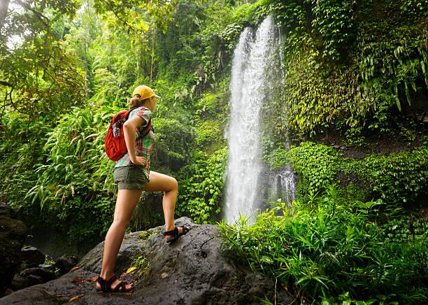 young woman backpacker looking at the waterfall in jungles. - lombok stockfoto's en -beelden