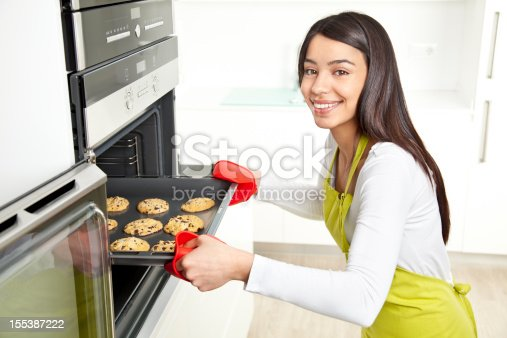 istock Young woman baking cookies at home 155387222
