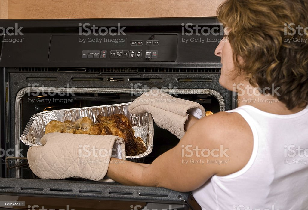 Young woman baking two chickens in an oven stock photo