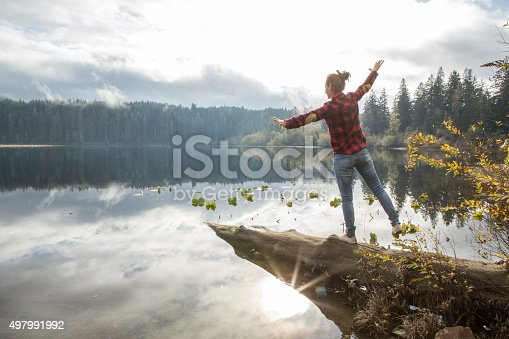 Young woman balances on a tree log above the lake. Beautiful pine tree forest and lake landscape. Shot on the Vancouver Island in British Columbia, Canada.