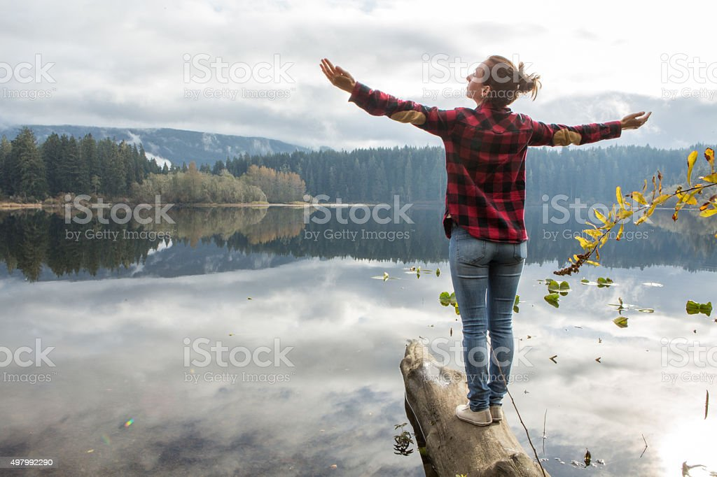 Young woman balances on a tree log above the lake stock photo