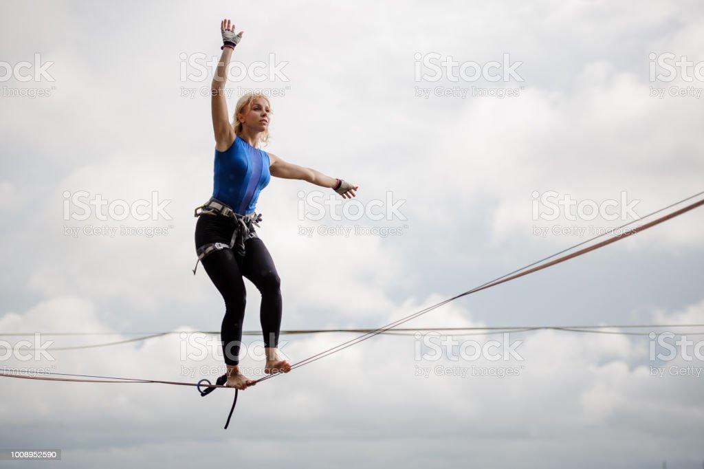 Junge Frau balancieren auf der Slackline-Seil und Blick in die Ferne – Foto