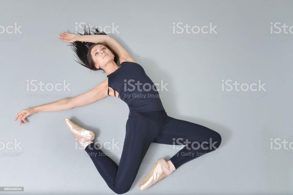 Bailarina de mujer joven mentira y que se extiende en el piso en estudio de ballet, vista desde arriba. - foto de stock