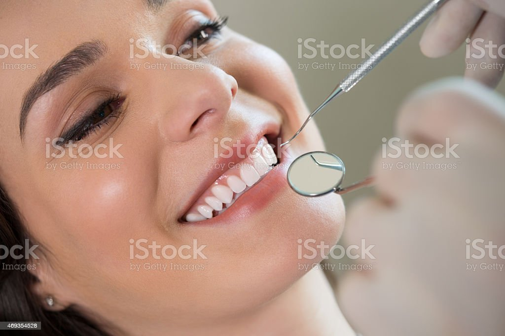 A young woman baring her teeth for the dentist to inspect stock photo