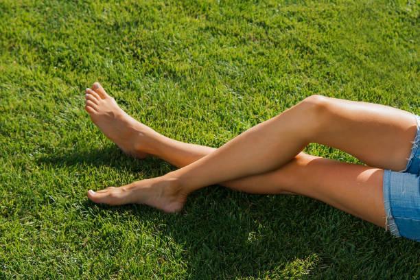 Jovem linda pernas enquanto estava deitada em um parque - foto de acervo