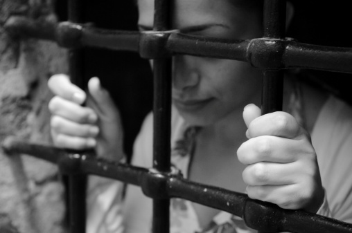 A young woman looking somber while holding onto prison bars. Focus on hand in foreground. Photographed in Syria (staged photo, not really a prisoner).