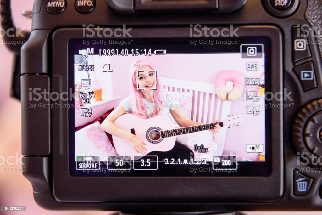 Young woman being filmed on video playing guitar in bedroom stock photo