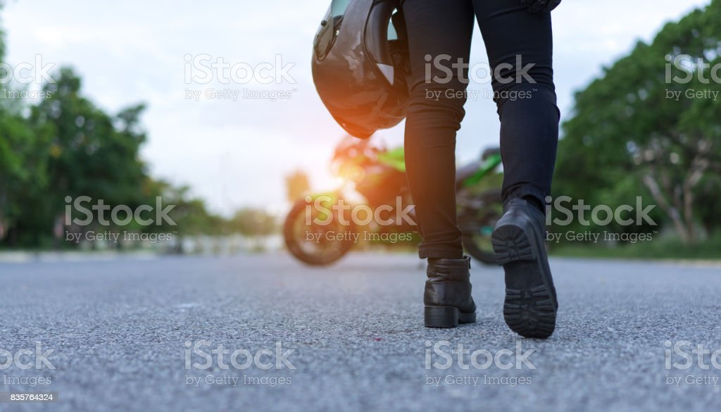 Young woman biker holding helmet equipment with jacket for safety protection when over high speed walking to motorcycle on street travel lifestyle. stock photo