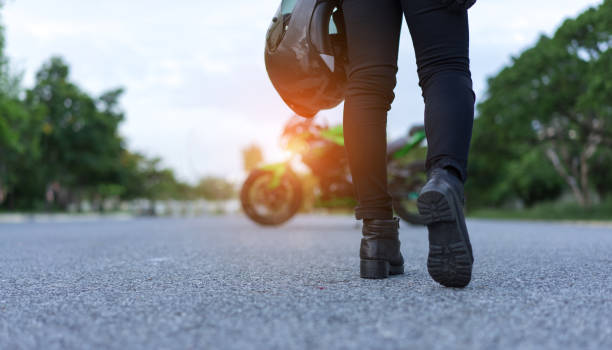 young woman biker holding helmet equipment with jacket for safety protection when over high speed walking to motorcycle on street travel lifestyle. - motorcycle stock photos and pictures