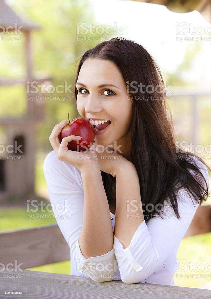 Young woman bites apple royalty-free stock photo