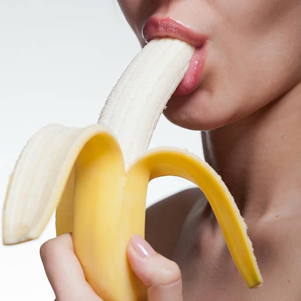 젊은 여자 물어뜯기 바나나 흰색 바탕에 그림자와 스톡 사진