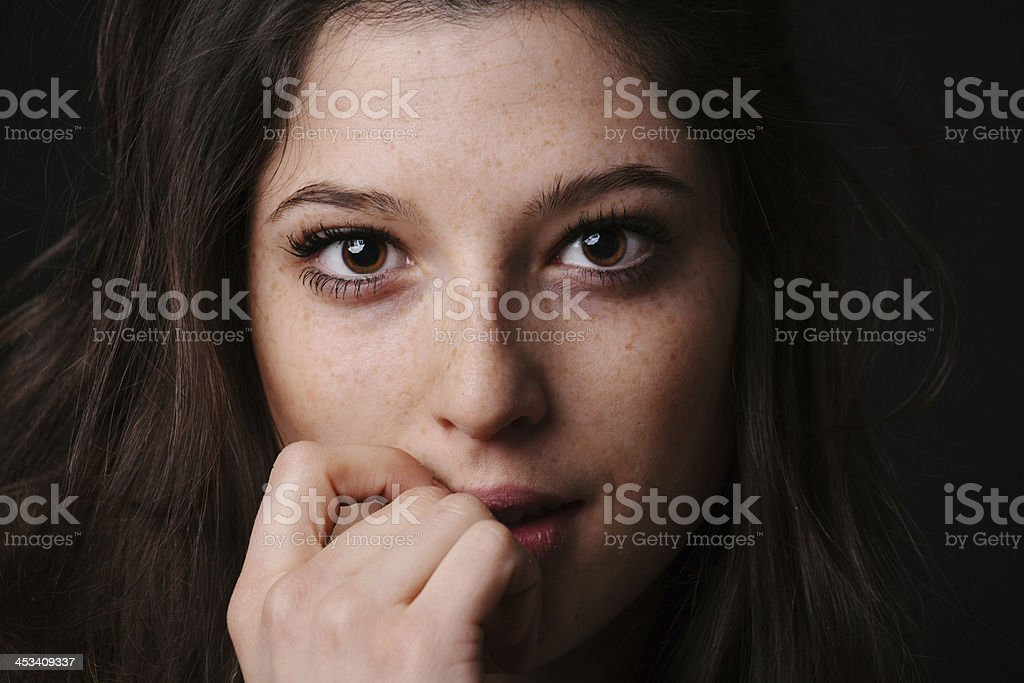 Young woman biting her knuckle stock photo