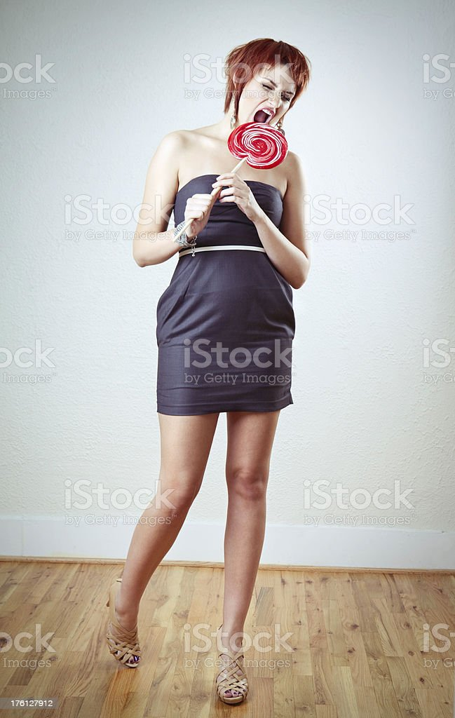 Young Woman Biting Red Lollipop stock photo