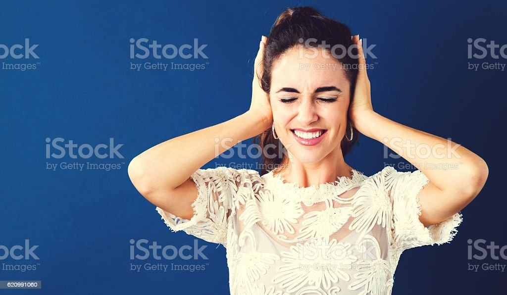 Young woman blocking her ears stock photo