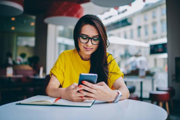 giovane donna blogger negli occhiali pubblicando un nuovo post sul proprio sito web e installando una nuova applicazione per la modifica di foto nei social network sul dispositivo smartphone digitale collegato a internet 4g gratuito - dispositivo informatico portatile foto e immagini stock