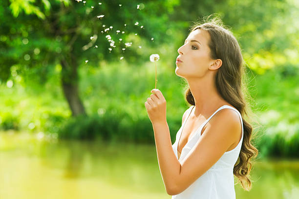 A young woman blowing a dandelion in nature