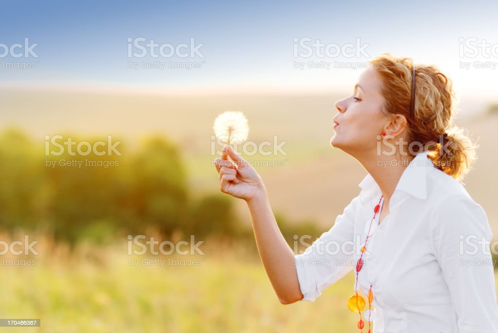 Young woman blowing a dandelion royalty-free stock photo