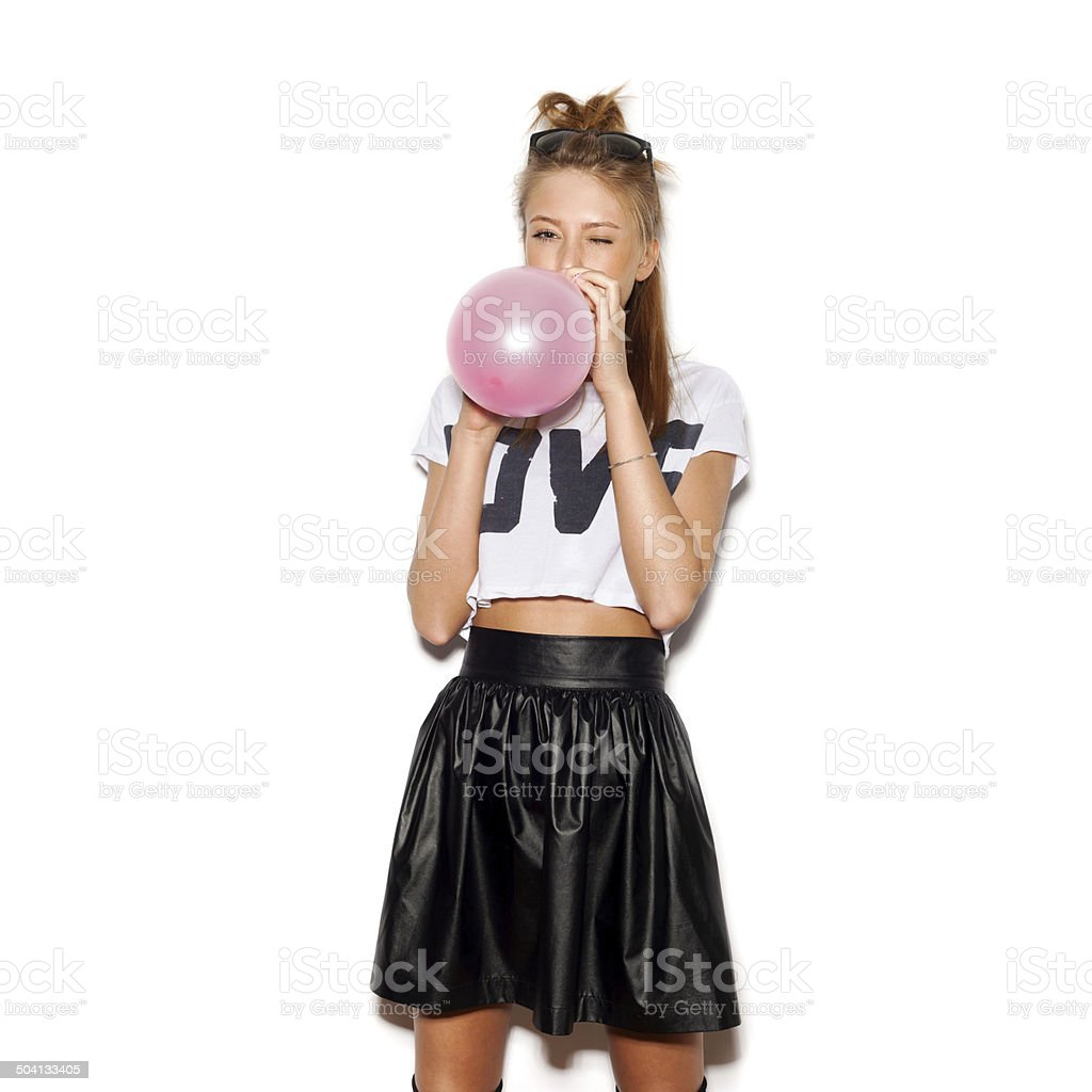 Young woman blowing a pink balloon stock photo