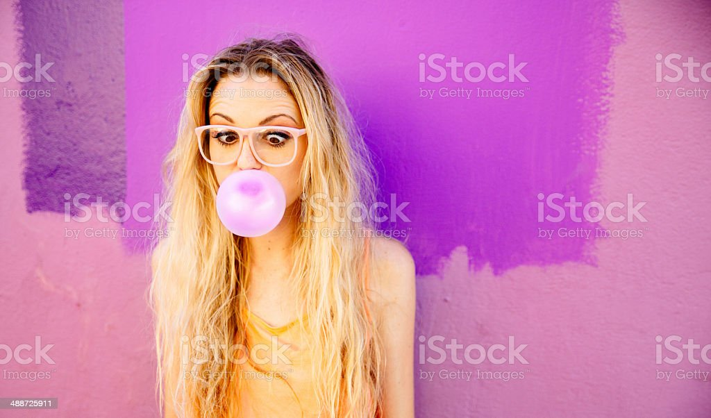 Joven mujer Soplando un rosa de chicle - foto de stock