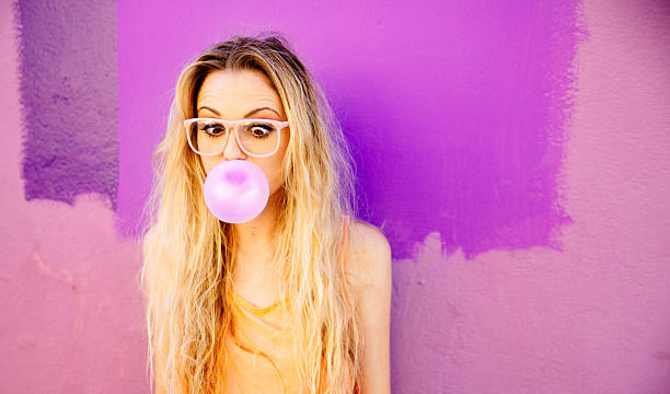Young woman blowing a pink bubble gum stock photo