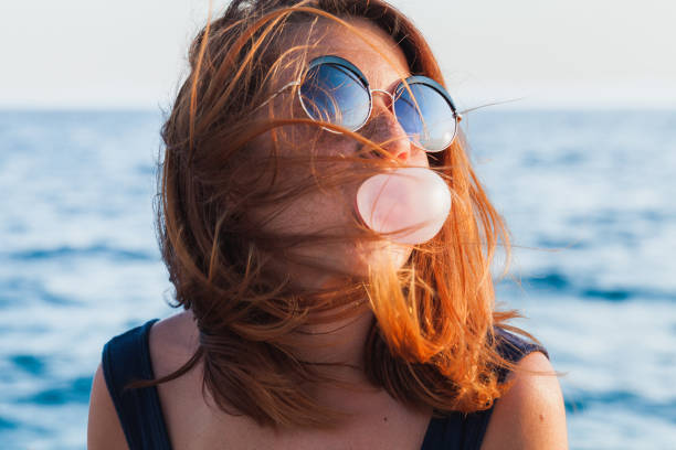 Young woman blowing bubble gum by the sea stock photo
