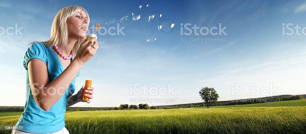 Junge Frau Blasen Blasen im grünen Feld – Foto