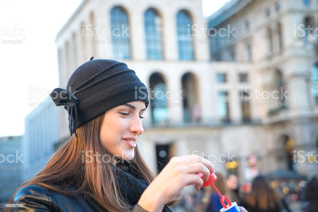 Young Woman Blowing Bubbles Outdoors In Urban Landscape royalty-free stock photo