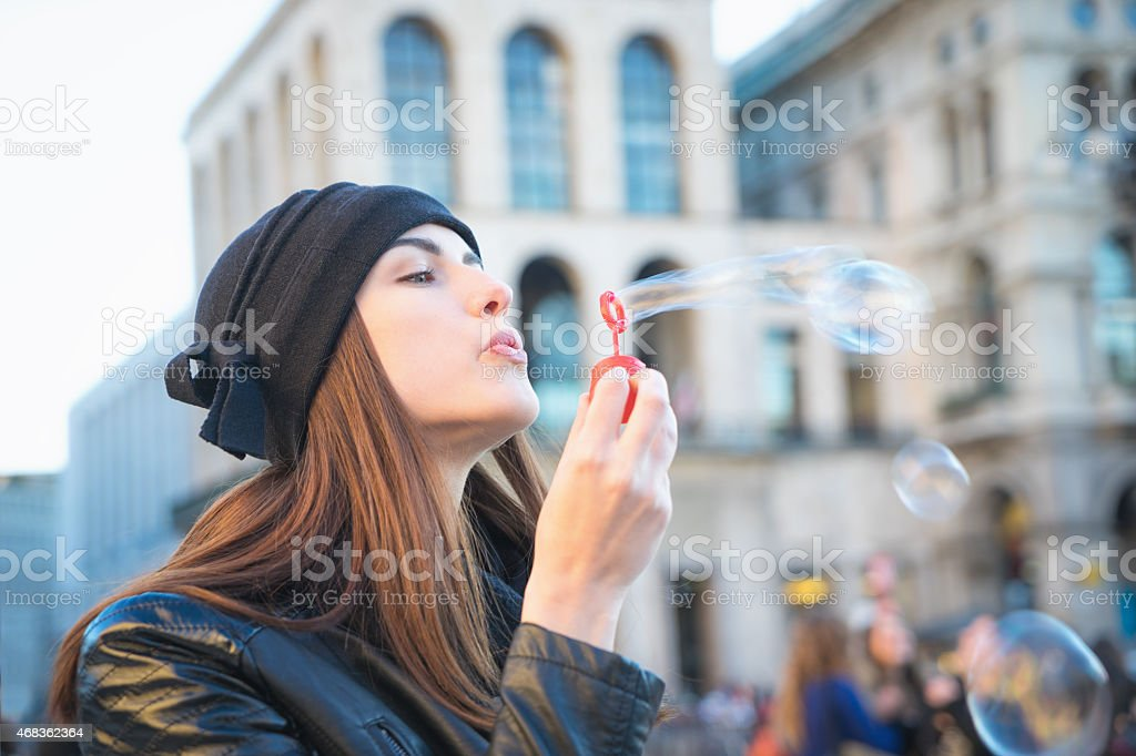 Young Woman Blowing Bubbles Outdoors In Urban Landscape stock photo