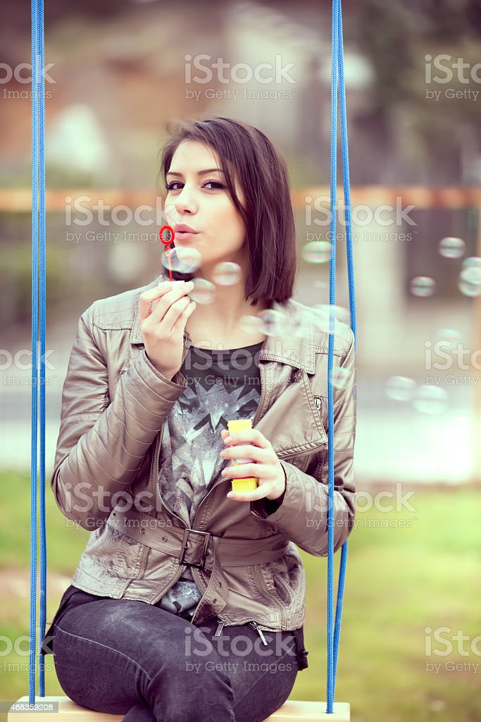 Young woman blowing bubbles swinging in the park royalty-free stock photo