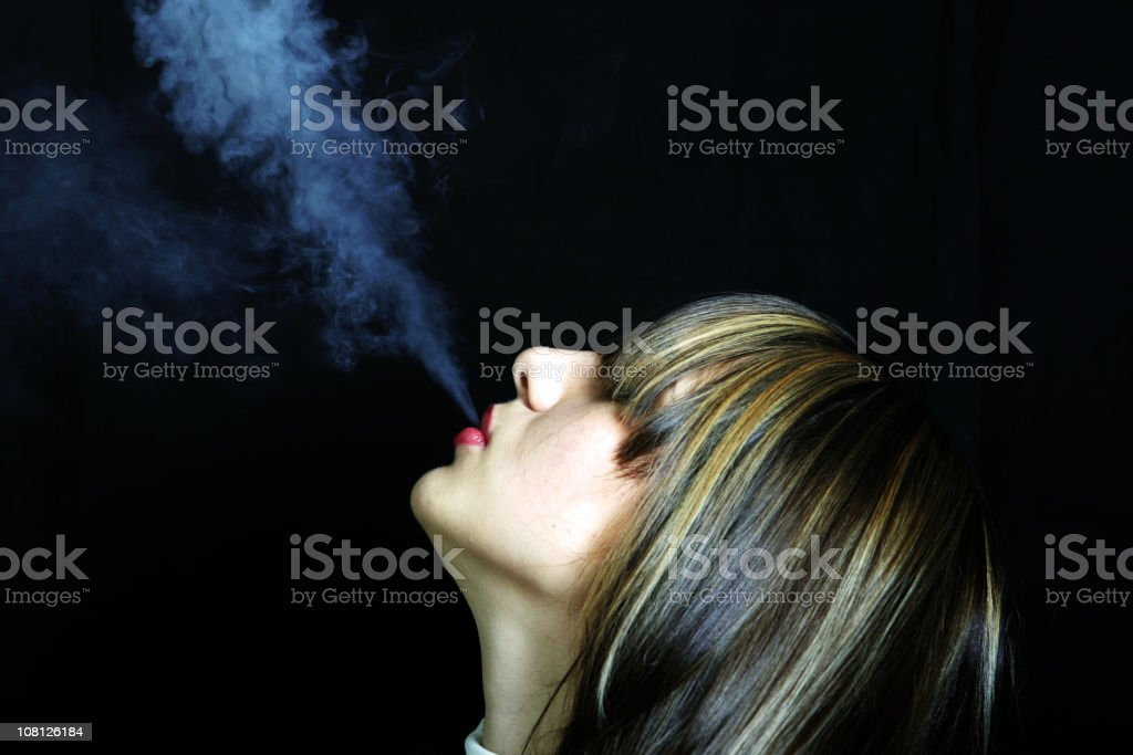 Young Woman Blowing Cigarette Smoke in Air on Black Background royalty-free stock photo