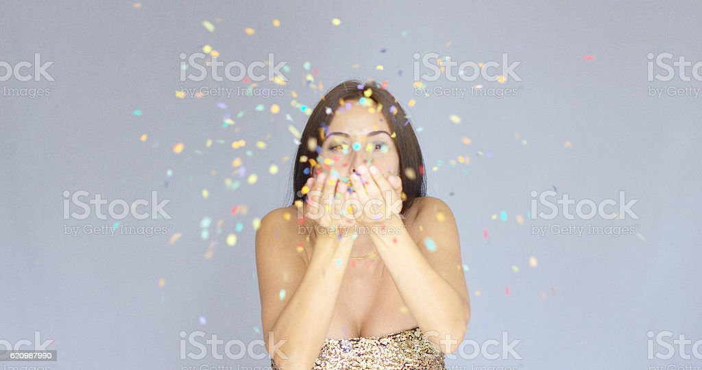 Young woman blowing colorful New Year confetti foto royalty-free