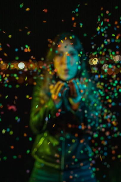 Junge Frau bläst Konfetti bei Nacht-Party – Foto