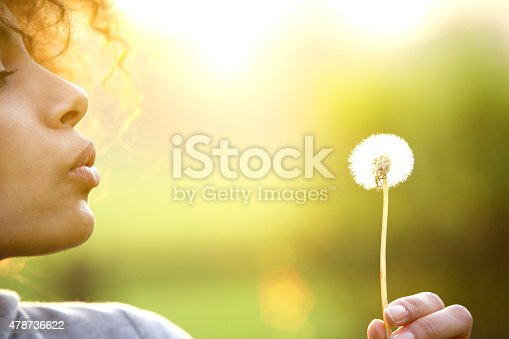 istock Young woman blowing dandelion flower outdoors 478736622