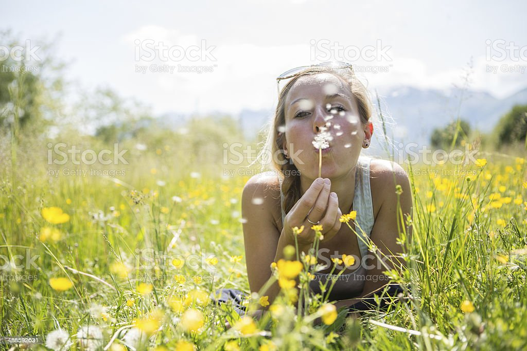 Young woman blowing flower in the field stock photo