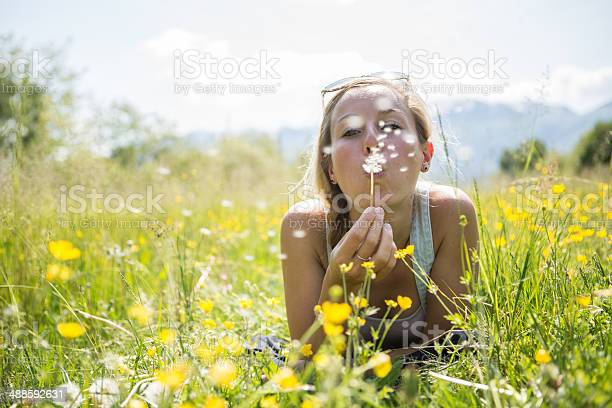 Photo of Young woman blowing flower in the field